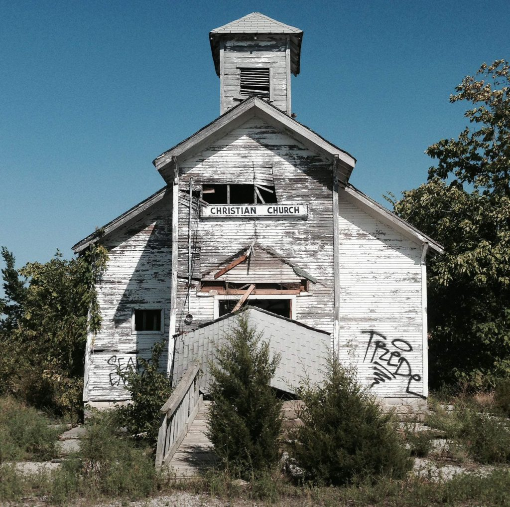 The parking lot for the abandoned Picher Christian Church at 201 S. Netta St. is now overgrown and the building is rapidly deteriorating. Just a year ago, the awning over the church doors was intact. (Lynda Waddington/The Gazette)