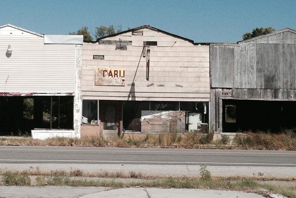 Motorists on U.S. Highway 69 are greeted by dilapidated store fronts in Picher, Okla. on Aug. 23, 2014. The middle structure was once home to Carlin's Hardware. The Brass Rail, a local drinking establishment was in the section on the right of the photo. To the left was once Hoppy's Pastime Mining Mini-Museum, a pool hall turned historic property that featured local live music on Monday nights, that once had an old, rusted iron ore can filled with rock on the front sidewalk. The concrete slab where the photographer stood was once the site of the Country Girls Cafe. (Lynda Waddington/The Gazette)