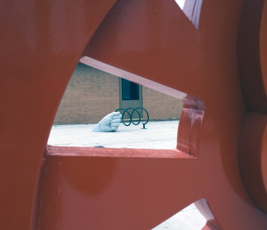A carved granite hand bike rack by Vermont artist Chris Miller is seen through one of the openings of a 17-foot abstract steam engine sculpture by Iowa artist Dan Perry on December 1, 2016. The two pieces are part of Marion, Iowa's ImaginArt in the Alleys, which is reinventing uptown alleyways for pedestrian enjoyment. (Lynda Waddington/The Gazette)