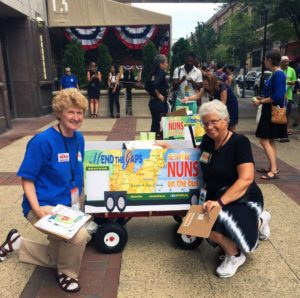 "Dubuque Catholic sisters Richelle Friedman (left), PBVM, and Marge Clark, BVM, pose beside one of the ""Nuns on the Bus"" wagons their group used to haul cold lemonade around the streets of Philadelphia on Thursday, July 28, 2016. (Lynda Waddington/The Gazette)"