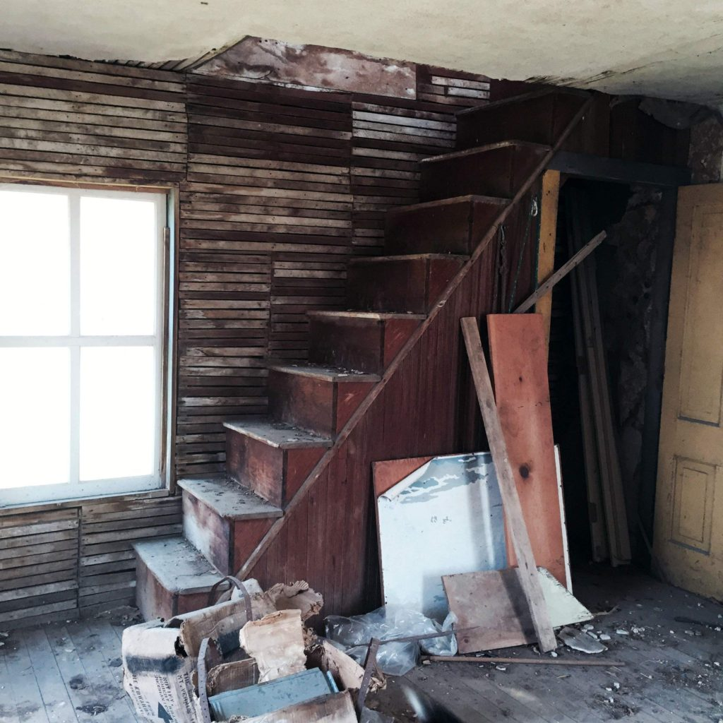 "While much of the plaster has fallen from interior walls on the main level of ""Little House,"" the wooden staircase leading to the upstairs sleeping room remains remarkably sturdy. Cedar County historians hope to move the house and its adjacent smokehouse from the Robinson farm south of Mechanicsville where they have stood for more than 100 years. Once a part of the historic Prairie Village, located south of Tipton, the buildings will be restored and preserved for future generations."