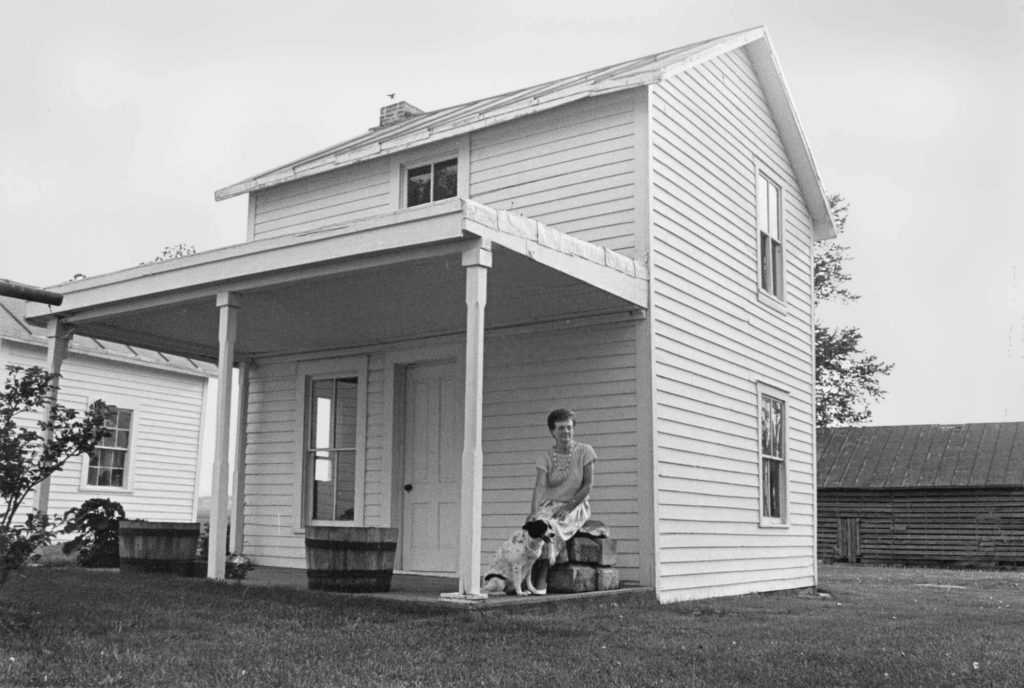 "Louise Robinson, now deceased, sat on the front porch of ""Little House"" with her dog, Mandi, in this June 1989 Gazette file photo. The weatherworn structures have been offered by Adam Robinson, Louise's son, to the Cedar County Historical Society. The organization hopes to relocate them to an historical village north of Tipton, but needs donations to build foundations for the buildings and begin preservation. Once home to early Cedar County farm families, the house is located south of Mechanicsville and behind a much larger home. The structures have been used for storage for more than 100 years."