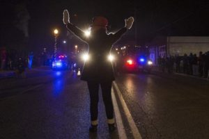 A female protester raises her hands while blocking police cars in Ferguson, Missouri, on November 25, 2014. On Wednesday the U.S. Department of Justice released two investigative reports, one finding no federal criminal wrongdoing by the Ferguson police officer that shot an unarmed 18-year-old and the other finding widespread racial bias in the local criminal justice system.