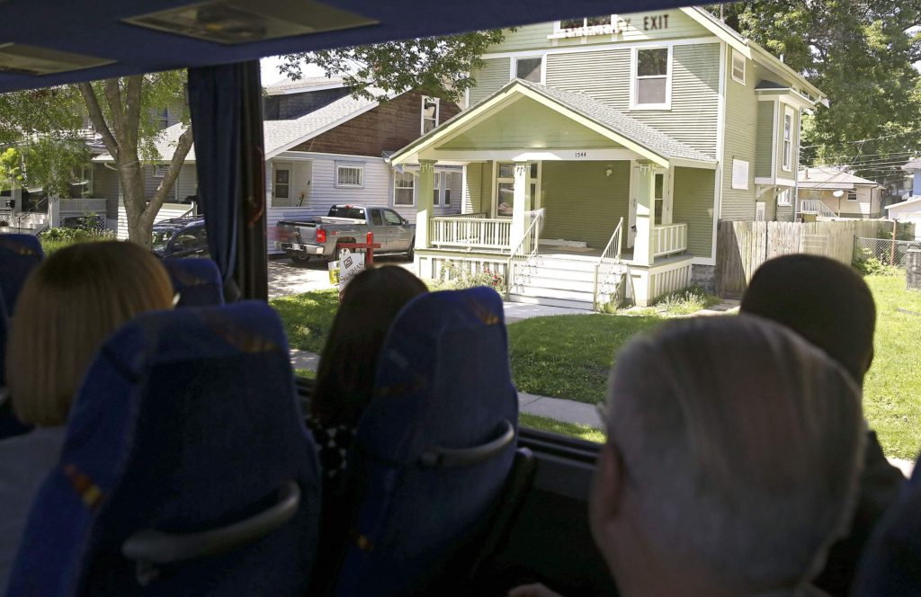 Area residents, elected officials and community leaders view affordable housing properties through the windows of a chartered bus during the Cedar Rapids Metro Affordable Housing Bus Tour in Cedar Rapids on Thursday, May. 25, 2017.