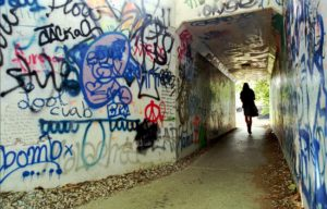 Placemaking - Students at the University of Iowa pass through a grafitti filled railroad tunnel along the Iowa River in this file photo.