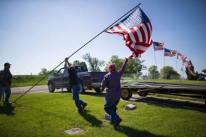 Memorial Day - Volunteers work to raise American flags along the edge of the cemetery in Oxford, Iowa.