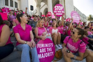 "Activists chant as they rally in support of Planned Parenthood on ""National Pink Out Day"" on the steps of City Hall in Los Angeles, California September 29, 2015. Planned Parenthood is embroiled in a debate about fetal tissue sparked by highly edited videos."
