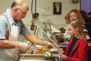 A volunteer places a sandwich on a student's lunch tray as she goes through the line at Benton Commuity Elementary in Keystone, Iowa. (File Photo)