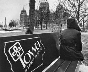 A woman sits on a bus stop bench east of the Statehouse in Des Moines in January 1983.
