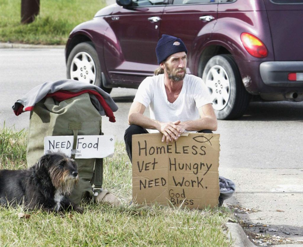 A panhandler works the intersection of Collins Road and Center Point Road NE in Cedar Rapids on Friday, Nov. 11, 2005.