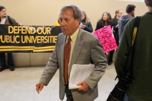 "University of Iowa President Bruce Harreld walks past protesters before a Feb. 23, 2016, town hall meeting at the Pomerantz Center in Iowa City. The contentious audience at times interrupted Harreld and later drew a rebuke from then-Board of Regents President Bruce Rastetter, who said the crowd should have been ""more professional."""