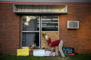 Ben Sunderlin places a sign of support near the window that was damaged during Saturday morning's attack at the Dar Al Farooq Islamic Center in Bloomington, Minn., on Tuesday, Aug. 8, 2017. More than a thousand people attended a community-wide show of support following the attack on the center.
