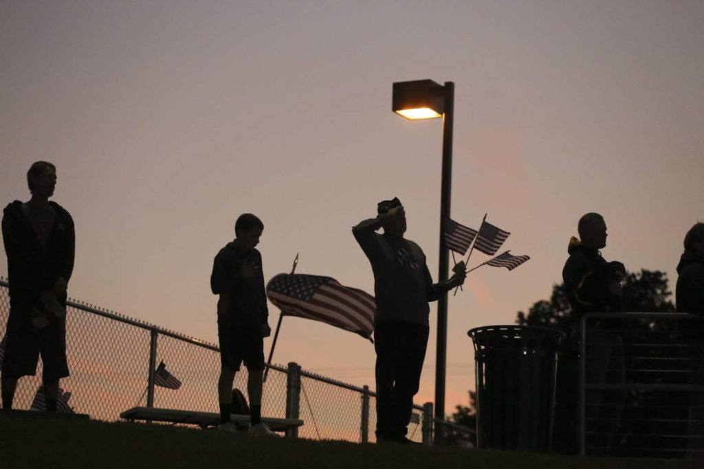 Veterans salute as the National Anthem is played before a high school football game in this file photo.