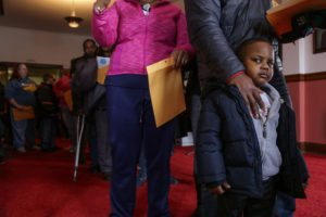 Lessons - Jaylen Smith, 4, of Flint waits in line with his father Keith Sanders to have blood samples taken to be tested for lead on Jan. 23, 2016 at the Masonic Temple in downtown Flint, Mich.