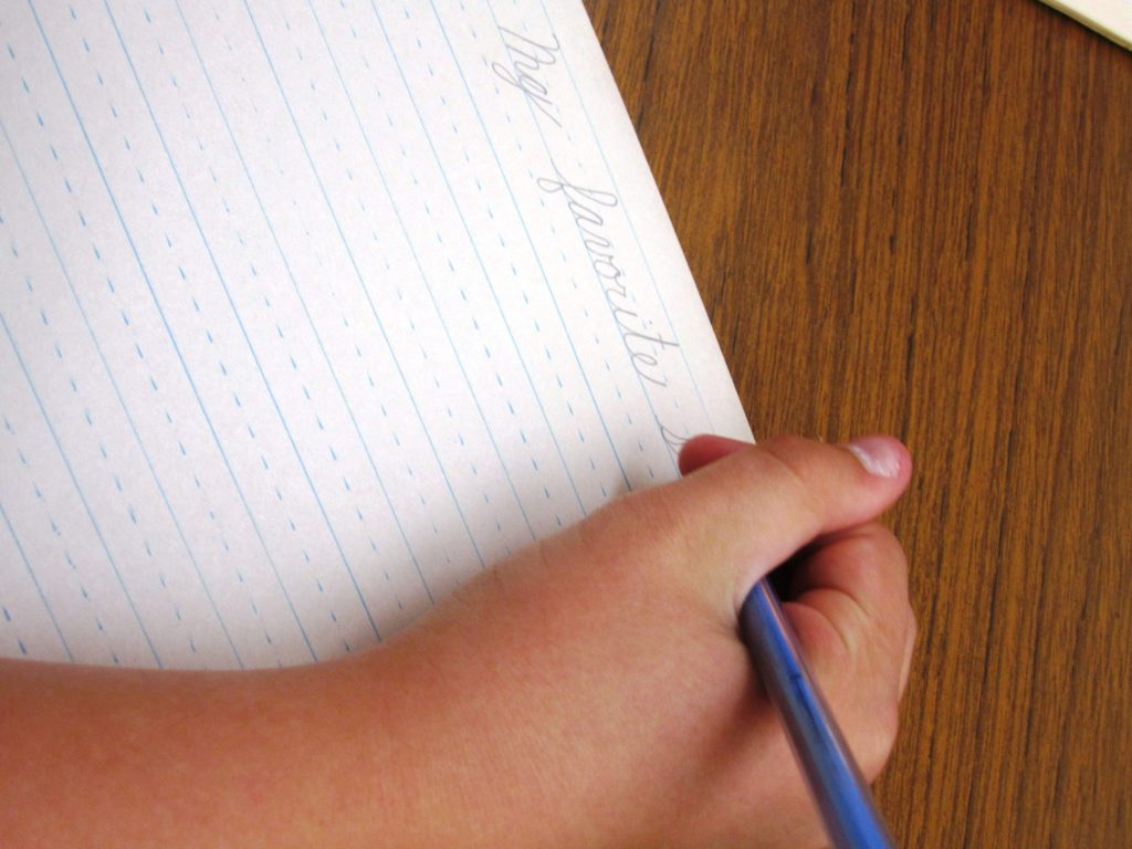 Civility - An elementary school student writes in cursive on a piece of paper.