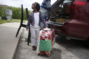 Immigrant families -- A 4-year-old Cedar Rapids girl helps her father unload supplies from a minivan for a newly-arrived family from Sudan in this 2015 file photo. The family is part of the CongoReform Association, an organization of immigrants helping immigrants.