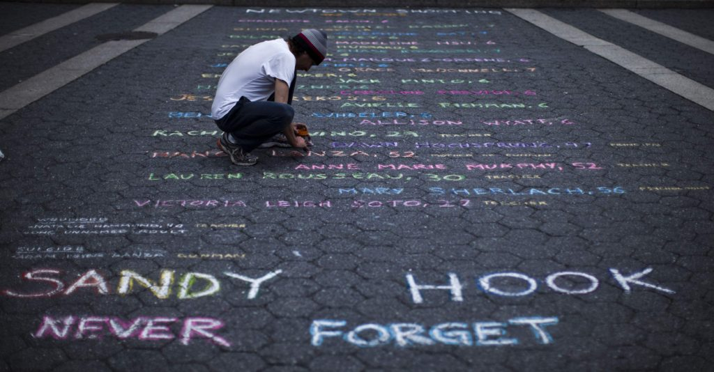 Newtown - Street artist Mark Panzarino, 41, prepares a memorial as he writes the names of the Sandy Hook Elementary School victims during the six-month anniversary of the massacre, at Union Square in New York, June 14, 2013.