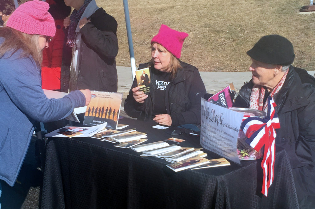 Sharon Poplawski (center) and Jeanne White (right) distribute free copies of the U.S. Constitution to attendees at the Women's March in Des Moines on Saturday, Jan. 20, 2018. The women and two friends founded the Sisterhood of Iowa last year and have pooled their personal resources to purchase and distribute the booklets.