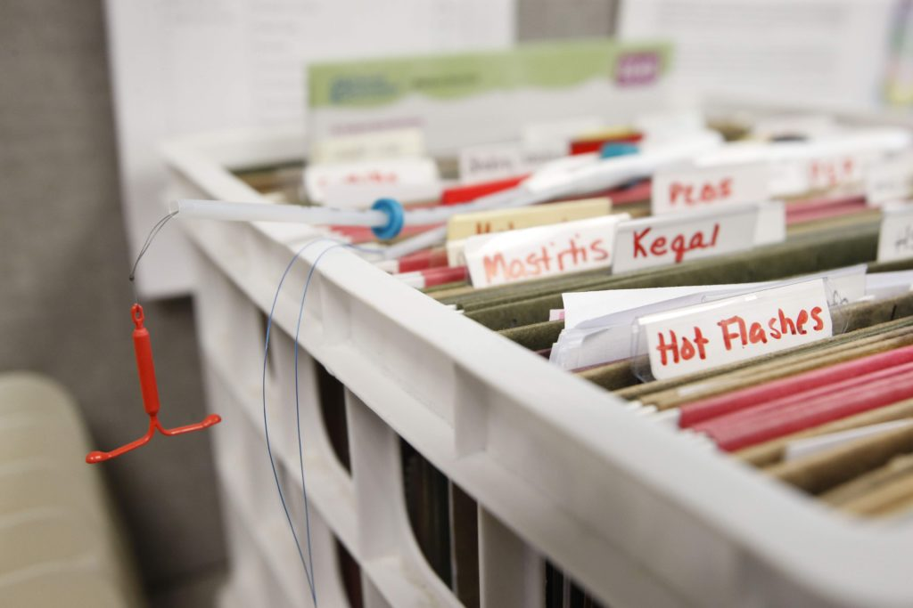 An intrauterine device used for training purposes hangs from a box of informational materials for patients at Planned Parenthood of the Heartland's Quad Cities Health Center in Bettendorf on Monday, June 26, 2017. The Iowa Legislature's decision to forego federal funding in order to exclude abortion providers from public family planning services resulted in the closure of four Planned Parenthood clinics as well as several rural health offices.