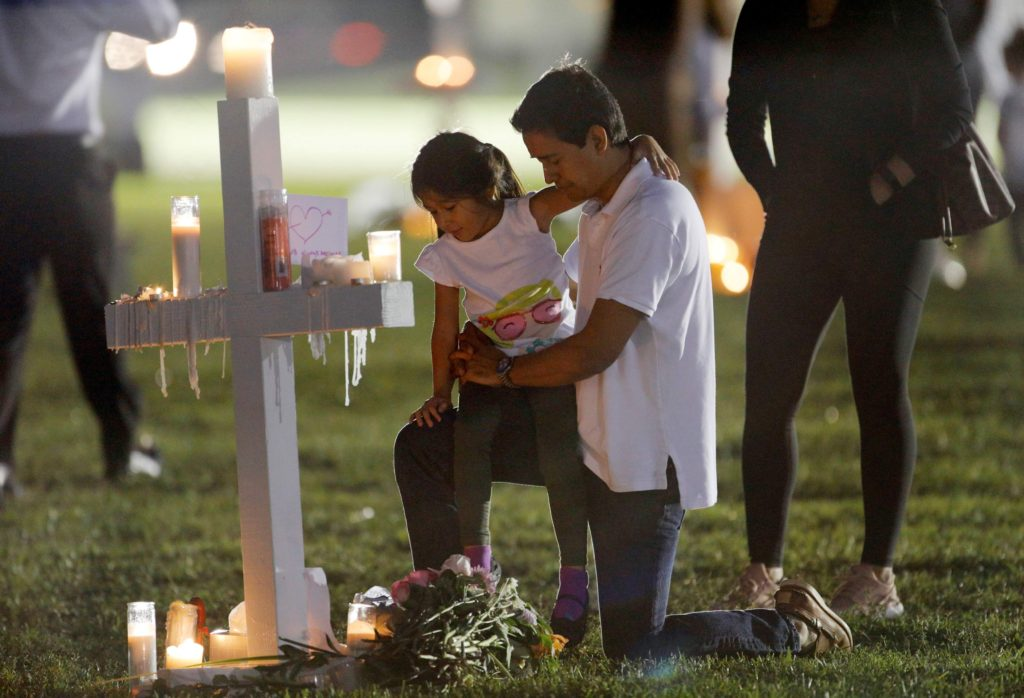 A father and daughter visit one of 17 crosses at a memorial for the victims of the shooting at Marjory Stoneman Douglas High School in Parkland, Florida, U.S. February 16, 2018.