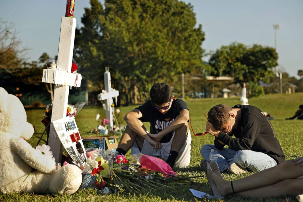Gun violence - Students, friends and family gather at the memorial crosses at Pine Trails Park in Parkland, Fla., to remember those where were killed and injured in the shooting at Marjory Stoneman Douglas High School, on Friday, Feb. 16, 2018.