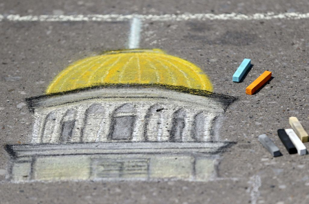 Sticks of chalk sit around a partially completed drawing of the Old Capitol Building during the third annual Rock the Chalk community art festival in downtown Iowa City on Friday, Aug. 10, 2018.