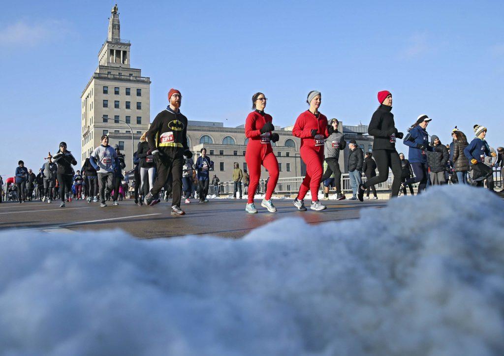 Runners pass a pile of snow on the 2nd Avenue bridge at the start of the Cedar Rapids Turkey Trot 5k run/walk in Cedar Rapids on Thursday, Nov. 22, 2018.